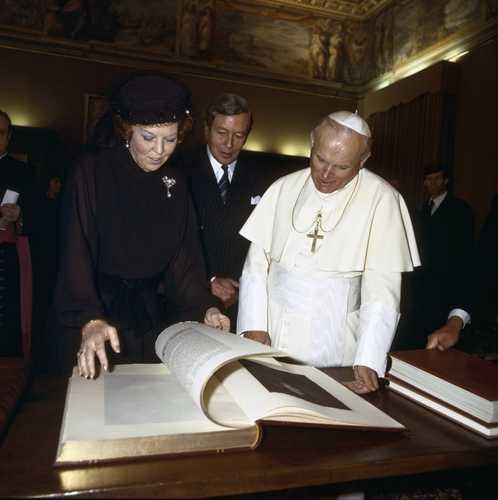 Paus Johannes Paulus II ontvangt koningin Beatrix en prins Claus 28 maart 1985 en toont een Nederlands boek in zijn bibliotheekzaal (foto Cor Mulder, ANP)