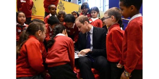 Prins William, hertog van Cambridge, in gesprek met scholieren in de jeugdbibliotheek