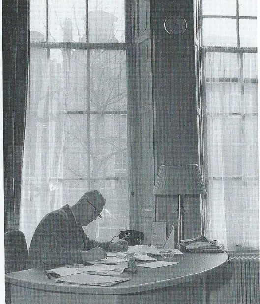 G.A.van Riemsdijk aan zijn bureau op de Keizersgracht als directeur van de openbare bibliotheek Amsterdam. Hij vervulde deze functie van 1948 tot 1964. In die periode kwamen er in Amsterdam 8 filialen bij, nam het aantal leden toe van 18.632 tot 56.436, het aantal uitleningen van 455.707 tot 2.046.387, de collectie van 165.141 naar 487.252 boeken, het aantal vestigingen van 9 naar 19 en het aantal medewerkers van 55 tot 101. Van 1964 was Van Riemsdijk - letterlijk en figuurlijk een boom van een man - directeur van de eerste bibliotheekschool (een HBO-opleiding) van ons land in Amsterdam. Na zijn pensionering schreef G.A.van Riemsdijk in drie delen de 'Geschiedenis van de openbare bibliotheek in Nederland': deel 1 Van de beginjaren tot mei 1940; deel 2: van mei 1940 tot mei 1945 en deel 3: van mei 1945 tot hert najaar 1958.