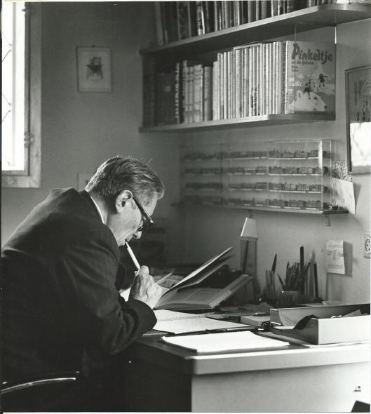 Dick Laan schrijven aan zijn bureau met een vitrine modelhuizen en een boekenrek met o.a. al verschenen Pinkeltje-boeken voor hem