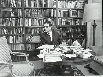 Godfried Bomans omringd door boeken en papieren