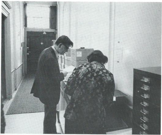 Fens (met onverbrekelijke sigaret) in de gang van de bibliotheek- en documentatieschool bij het kopieerapparaat. Op dec rug gezien lerares  en roostermaakster Ans Schonebaum