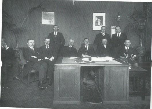 Installatie van burgemeester N.L.M.Tilman in 1922. Van links naar rechts (de man half op de foto helemaal links onbekend): P.van Aalst, W.Prins, J.Huysmans (staand), P.Bakker, de nieuwe burgemeester Tilman (in 1925 geschorst en ontslagen), J.F.van Lierop, C.Loeff (staand, loco-burgemeester P.Zeestraten (staand) en J.Dubbis.