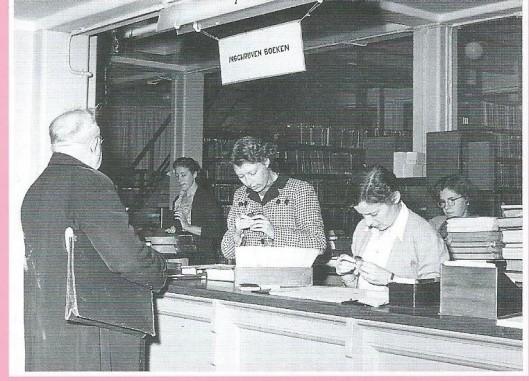 Rechts vooraan achter de uitleenbalie docente mej. Ans Schonebaum in de tijd dat zij nog werkte bij de openbare leeszaal en bibliotheek van Amsterdam in 1952