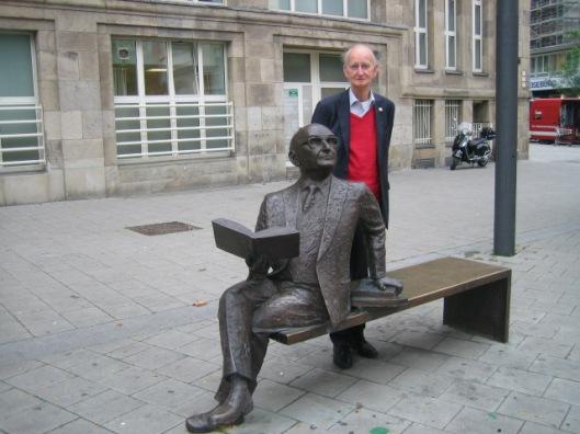 Hans Krol bij sculptuur van de Frans-Europese staatsman Robert Schuman (1866-1963) In Duisburg
