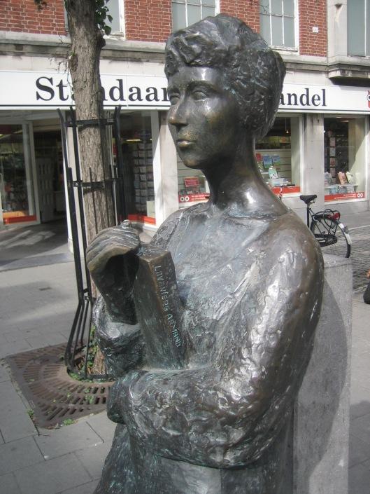 Lezende vrouw voor de Standaard Boekhandel in de Naamsestraat, Leuven
