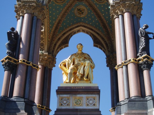 'Albert Memorial' Beeld in brons, in een granieten koepel. gelegen in de Kensington Tuinen nabij de Royal Albert Hall te Londen. Een monument ter ere van de cultuurminnende prins-gemaal van koningin Victoria, prins Albert van Saksen-Coburg (1819-1861). In zijn rechterhand houdt hij een boek vast.