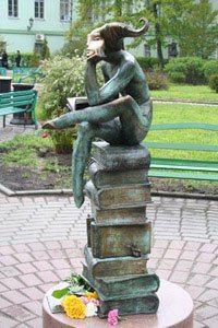 Persoon op bronzen boeken in Pierre le Gand