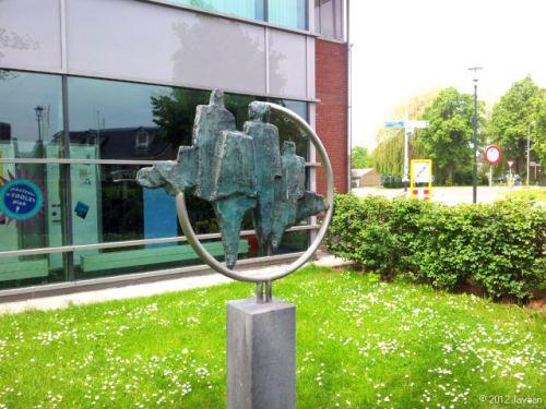 Sculptuur: bibliotheekbezoekers. Groep gestileerde personen (man, vrouw en kind) in een aluminium cirkel. Bij het gebouw van de openbare bibliotheek 's- Gravendeel geplaatst, bij de opening op 17 september 2005