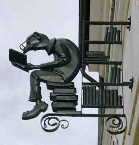 Uithangbord van lezer en boeken van boekhandel Knoblauchmare in Annaberg-Bucholz, Duitsland (Volta Meia)