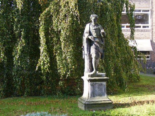 Beeld voorstellende de legendarische uitvinder van de boekdrukkunst Laurens Janszoon Coster; door Gerrit van Heerstal, circa 1742. In tuin Prinsenhof Haarlem nabij het stedelijk gymnasium