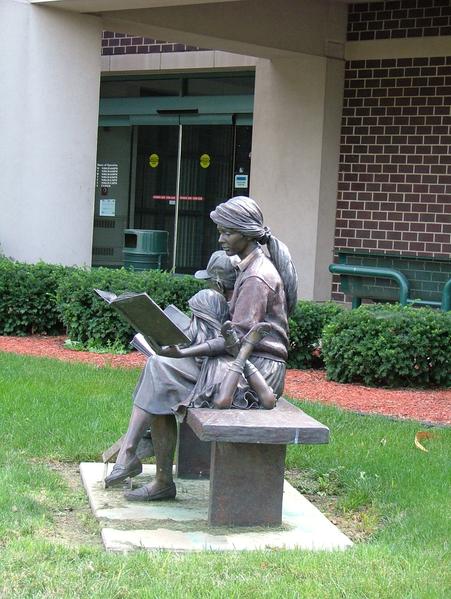 Voorlezende moeder in brons. Sculptuur bij de Danville Public Library, Illinois, USA (Wikipedia)