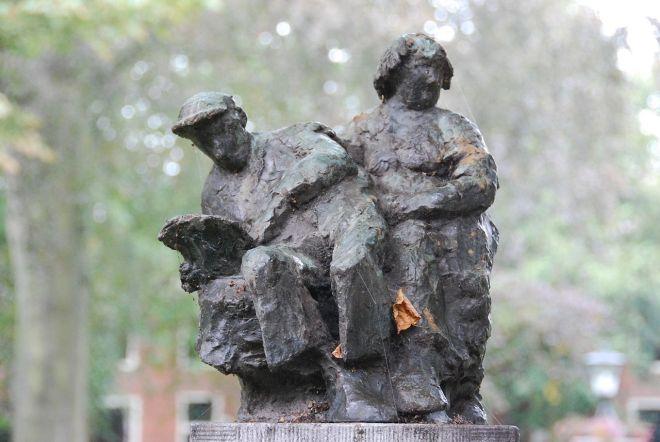 Zittend paar in brons, waarbij man met boek. Door Cor Hund, in 1963 geplaatst in de Grote Houtstraat bij het Proveniershofje te Haarlem