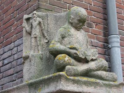 Lezend kind in zandsteen door Hildo Krop (1884-1970), Dongestraat Amsterdam. Is toe aan restauratie (Leesbeelden)