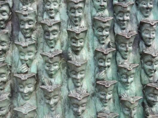 'Lecteurs de la Rochelle' In brons vervaardigd door Bruce Krebs op een walmuur nabij de oude poort van La Rochelle, Frankrijk