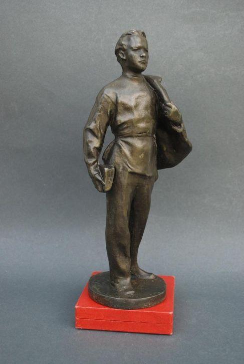 In veelvoud gemaakt beeldje van een jonge Lenin met jas over de schouder en boek in de hand