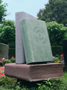 Drie boeken van natuursteen op een graf in Noord-Brabant (Fleuren)