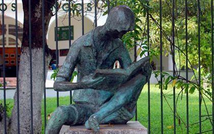 Zittende jongen lezenfr in een boek voor de Los Mangos bibliotheek in Mexico. Bronzen beeld van de kunstenaar Ramiz Barguet.
