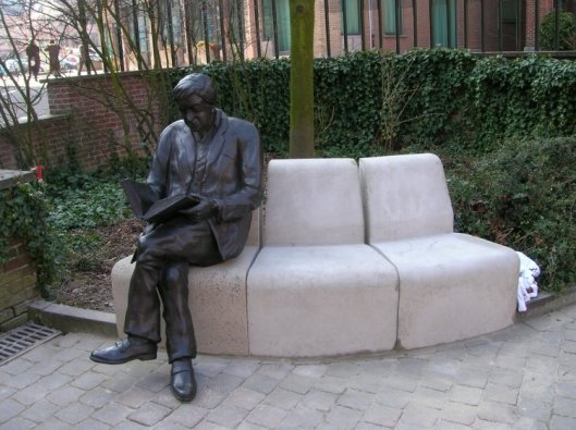 Bronzen beeld van een lezer op een zitbank in Mouscroun, België