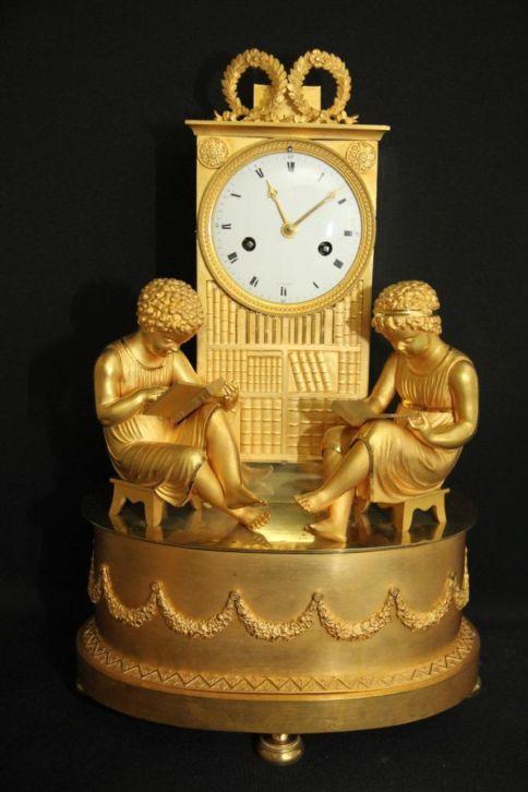Pendule in brons, geflankeerd door lezers