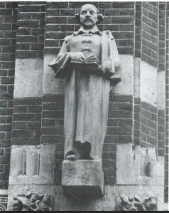 Joost van den Vondel met boek. Amsterdam, Warmoesstraat tegen gevel van de Effectenbeurs. In 1937 in zandsteen vervaardigd door Gerarda Rueter