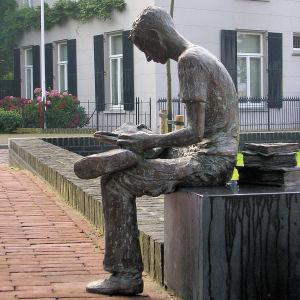 Lezende student, bronzen beeld van Lia Krol uit Erichem, geplaatst nabij de vm. Latijnse school in Gemert, Noord-Brabant