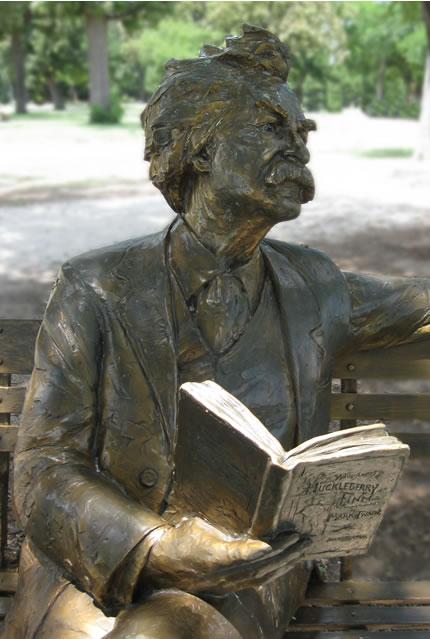 Beeld van de Amerikaanse schrijver Mark Twain met in zijn hand 'Huckleberry Finn' in Trinity Park, Fort Worth, USA