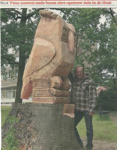 Uit het hout van een omgewaaide boom gesneden uil als symbool van wijsheid op boeken in de tuin het zorgcentrum Sint Jacob in Haarlem