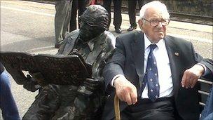 Beeld voor Nicholas Winton, in 2010 onthuld in Windson, met de 101-jarige rechts in eigen persoon. Winton, de Britse Schindler genoemd, redde tijdens WOII in Tsjechoslowakije honderden kinderen van deportatie naar Duitse concentratiekampen (BBC)