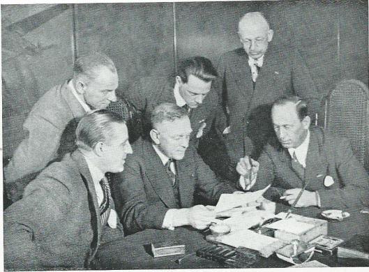 De roemruchte recordvlucht van de Pelikaan leverde heel wat ervaringsmateriaal op. De bemanning bespreekt de toch met KLM-directeur Albert Plesman. Zittend van links naar rechts: de heren Soer, Plesman, Smirnoff, staand v.l.n.r. Grosfeld, Van Beukering, Martin.