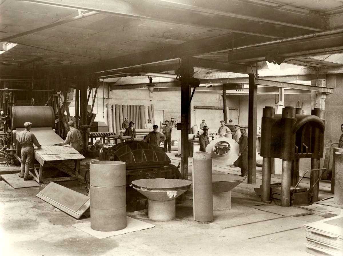 Eén van de zalen van de n.v. Nederlandse Fabriek van Asbest-Cement Platen 'Martinit' in Amsterdam. Werknemers zijn aan het werk. Asbest platen en pijpen staan gereed. Foto uit 1930 (Geheugen van Nederland)