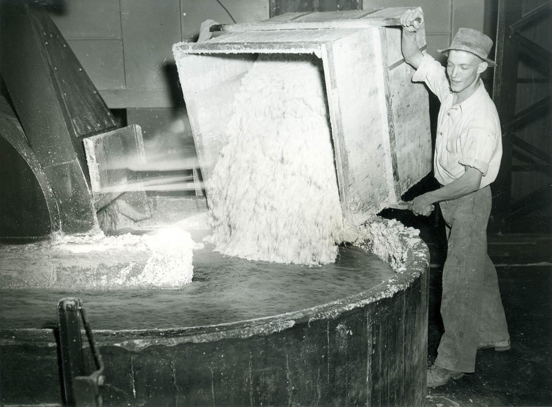 Ruw gemaakte asbest in een mengmachine gekiept waar water en asbest worden toegevoegd ten behoeve van asbestplaten, o.a. gebruikt voor daken. Hier op een foto uit Zuid-Afrika.