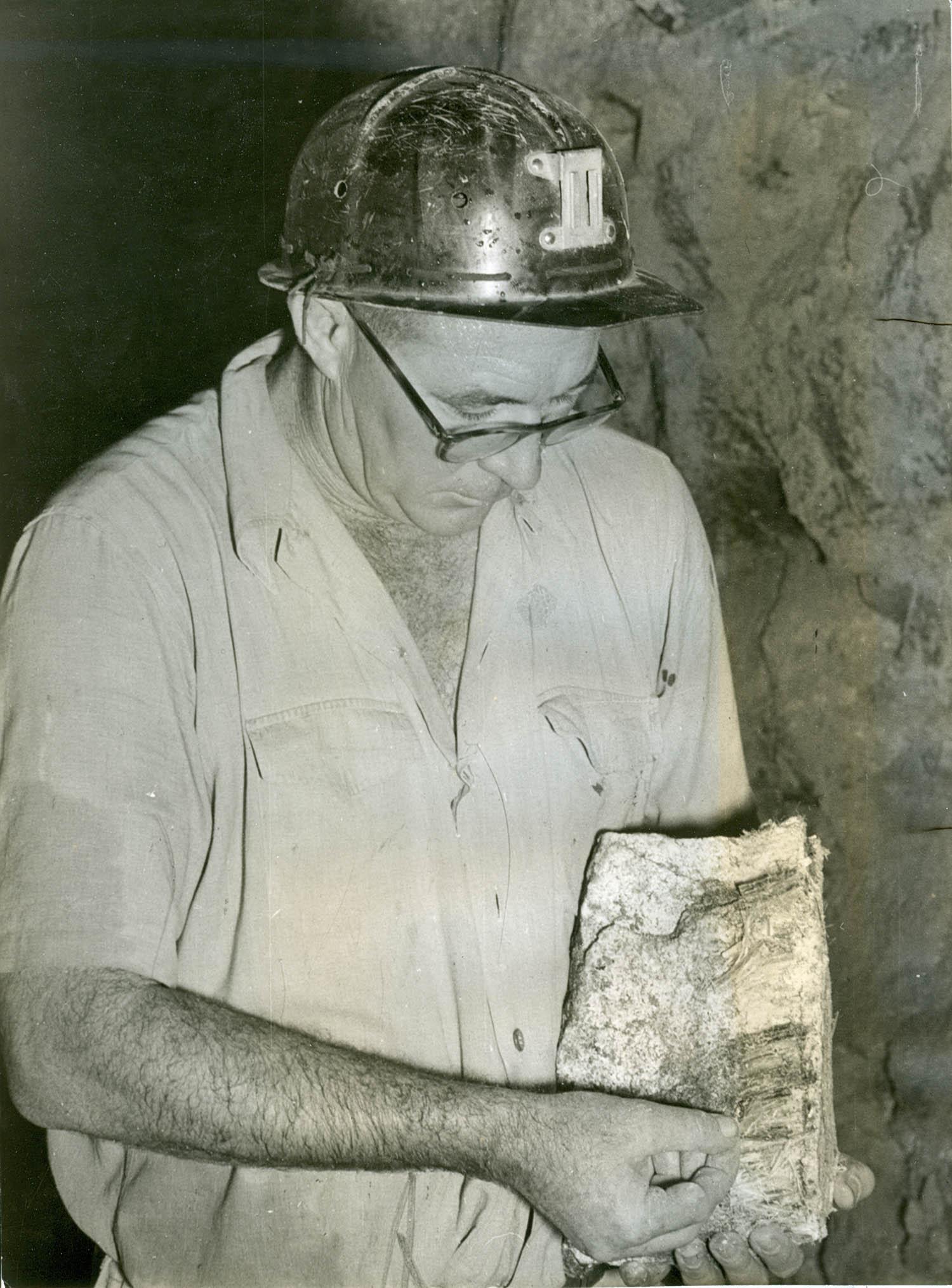 Een mijnwerker uit Rhodesië/Zimbabwe met chrysotiel-asbest in de hand met afgezien van een helm zonder verdere bescherming