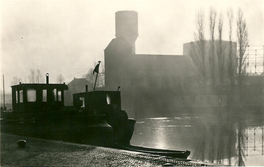 Ansichtkaart uit omstreeks 1950 van een schip aan de kade van de haven en de gasfabriek en watertoren nabij de Nijverheidsweg op de achtergrond.