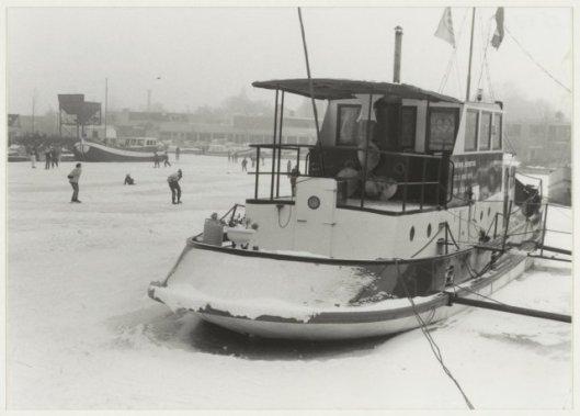 Schaatsers in de haven Heemstede. Rechts de sleepboot van oud-schipper P.van Wijk (NH ARCHIEF, Cees de Boer, 1985).
