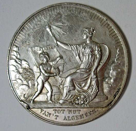 Penning uitgegeven ter gelegenheid vn het 50-jrig bestaan van het Nur in 1834.Symbolische voorstelling van een vrouw met in de linkerhand een hoorn des overvloeds en in de rechterhand een fkkel. Opschrift op een open boek op een lessenaar 'voor allen'.