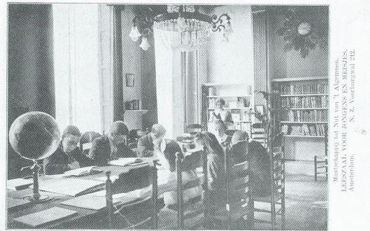 Prentbriefkaart van de in 1912 geopende gemengde leeszaal voor jongens en meisjes van het Nut aan de Nieuwe Zijds Voorburgwal 212. Aan het eind zien we directrice, later van de openbare bibliotheek, mej. Annie C.Gebhard.