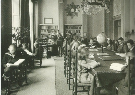 De kinderleeszaal van het Nut aan de N.Z.Voorburgwal 212 in Amsterdam. Foto die op 18 november 1916 in het blad 'Eigen Haard' verscheen. Citaat: 'Het Fransche zaaltje met de kolommen en hoog wit plafond ziet er vrolijk en licht uit en heeft niets straks of strengs, ondanks de boeken, die men overal ziet. Dit komt wel voornamelijk doordat de boeken niet in bruin 'kaftpapier-uniform' zijn, maar heel gewoon in gezellige bandjes. Op de tafel staat wel een aardbol, maar er staan ook bloemen en er ligt een warm geel kleed. Vooral de tafeltjes langs de kranten bij de ramen, elk met een bloempot erop en stoelen rondom, noodigen uit om er te gaan zitten.