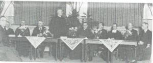 Een vergadering in het Vereenigingsgebouw aan de Herenweg. Staande pastoor H.IJzermans en rechts van hemplebaan Westerwoudt. Helemaal rechts zit Jac.H.Kramer, die sinds 1930 kerkmeester was van de S.Bavokerk in Heemstede