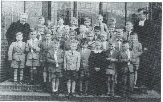 Eerste Heilige Communie, 1955. Achteraan links pastoor Janssen Schmidt en helemaal rechts broeder Bernardus (foto L.Glas)