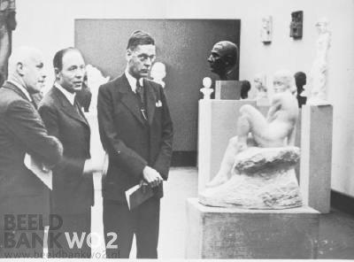 Dr.Th.Goedewaagen, secretaris-generaal van het departement van Volksvoorlichting en Kunsten, opende 1 maart 1943 tentoonstelling van beeldhouwwerk in Amsterdam. V.l.n.r. Dirk Wolbers, Eduard Gerdes en dr.Th.Goedewaagen. Na 1942 zag Dirk Wolbers in dat zijn collaboratie met Duitse autoriteiten onterecht was (Beeldbank WOi11)