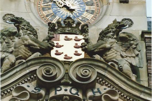 Nogmaals het wapen van Heemstede in de voorgevel van het raadhuis, met merletten en vrijkwartier, alsmede de schilhouders en kroon