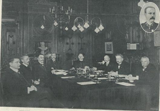 Foto van de eerste ministerraad van het nieuwe kabinet op woensdag 12 februari 1908. Van links naar rechts de namen van de 8 ministers: A.S.Talma, minister van Landbouw, Nijverheid en Handel, luitenant-generaal F.A.H.Sabron, minister van Oorlog, mr.M.J.C.M.Kolkman, minister van Financiën, vice-admiraal J.Wentholt, minister van Marine, mr.A.P.Nelissen, Minister van Justitie; jhr.mr.R.de Marees van Swinderen, minister van Buitenlandse Zaken, mr.Th.Heemskerk, minister van Binnenlandse Zaken, mr.J.G.S.Bevers, minister van Waterstaat. In de rechterbovenhoek A.W.F.Idenburg, minister van Koloniën, die op dat moment in het buitenland vertoefde.