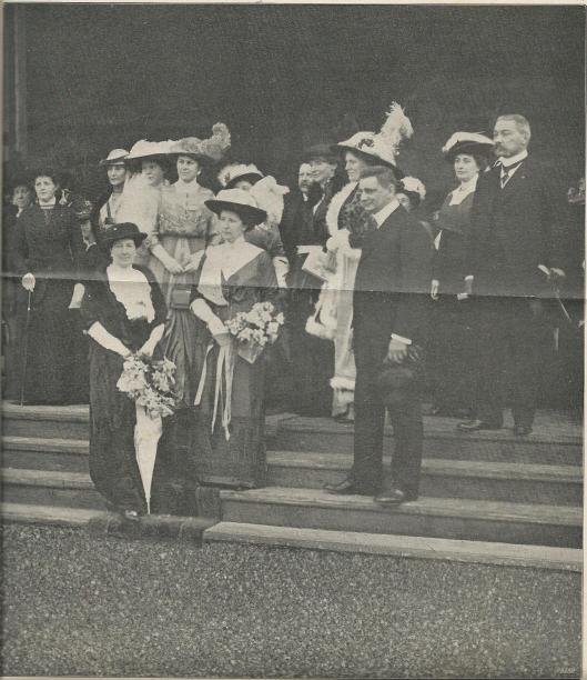 De feestelijke opening van de expositie 'De Vrouw 1813-1913'te Amsterdam. Op de voorgrond van links naar rechts: mevrouw van Loon, mw. Roëll (echtgenote van de burgemeester), minister Talma. Iets hoger rechts: mr.dr.W.P.van Leeuwen, commissaris der Koningin in Noord-Holland; op de bovenste trede (achter bestuurslid mw.vn Loon en mw.Roëll: dr. Mia Boissevain, pesidente van het bestuur, mw. van Leeuwen en burgemeester Roëll (De Prins, 10 mei 1913)