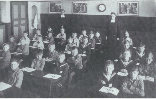 Foto uit 1931 van de eerste klas van de Jacobaschool met broeder-directeur Hyacintus en rechts Broeder Bernardinus Baar