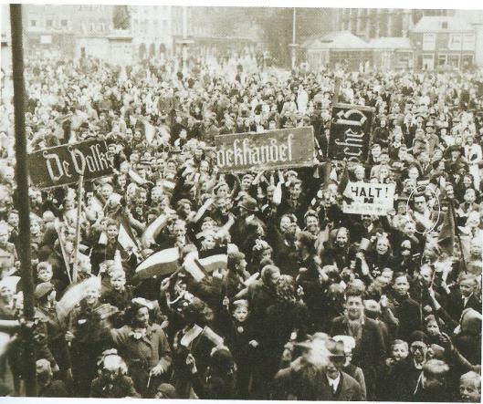 Haarlemmers vieren de bevrijding. Rechts naast het bord 'Halt' is Godfried Bomans te zien