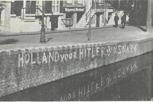 Opschrift met propaganda voor de NSNAP gekalkt aan de wal van een van de Amsterdamse grachten