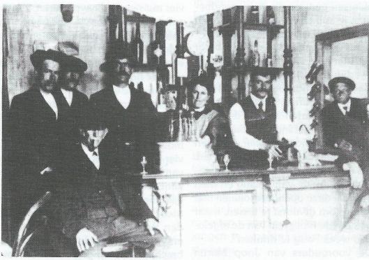 Interieur van het café  N.J.Martin op de hoek van de Kerklaan en de Raadhuisstraat omstreeks 1910. Van links naar rechts; Van der Klashorst, onbekend, zittend met pijp: grootvader Brouwer, de Bruin, mevrouw Martin-Brouwer, N.J.Martin, onbekend en geheel rechts een persoon met bijnaam 'Scheve Dirk'.