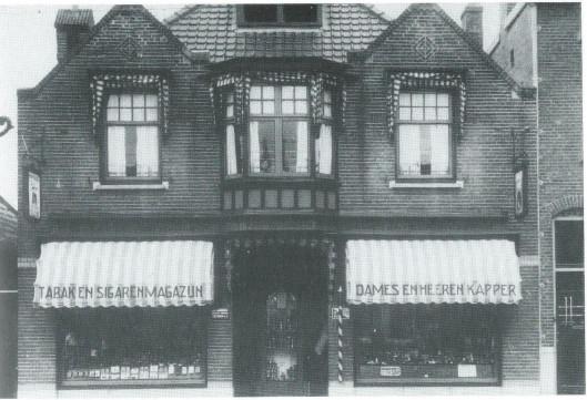 Veelzijdig was de firma F.Oosterhoorn, in het uit 1910 daterende pand Raadhuisstraat 6, met uitbreiding in 1934, Raadhuisstraat 8, bestaande uit dames- en herenkapsalon en manicure (achter), parfumerieën, lederwaren (recvhts) en een tabkswinkel (links). Dochter Tineke Oosterhoorn kijkt boven vanuit het middenraam. Zij herinnerde zich dat op later leeftijd dat het vaak erg gezellig was en vooral op zaterdagavond soms een sociëteit.