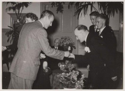 Tijdens een receptie in Groenendaal reikt burgemeester (tevens vaste klant) van Adam Zwarter, mr.A.G.A.Ridder van Rappard (links)  een gemeentelijke erepenning van verdienste uit.